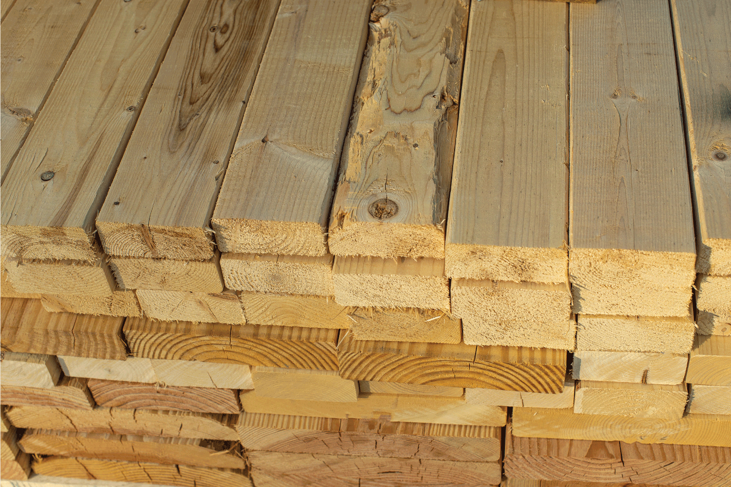 A stack of wood 2x4 beams, view of rough cut ends