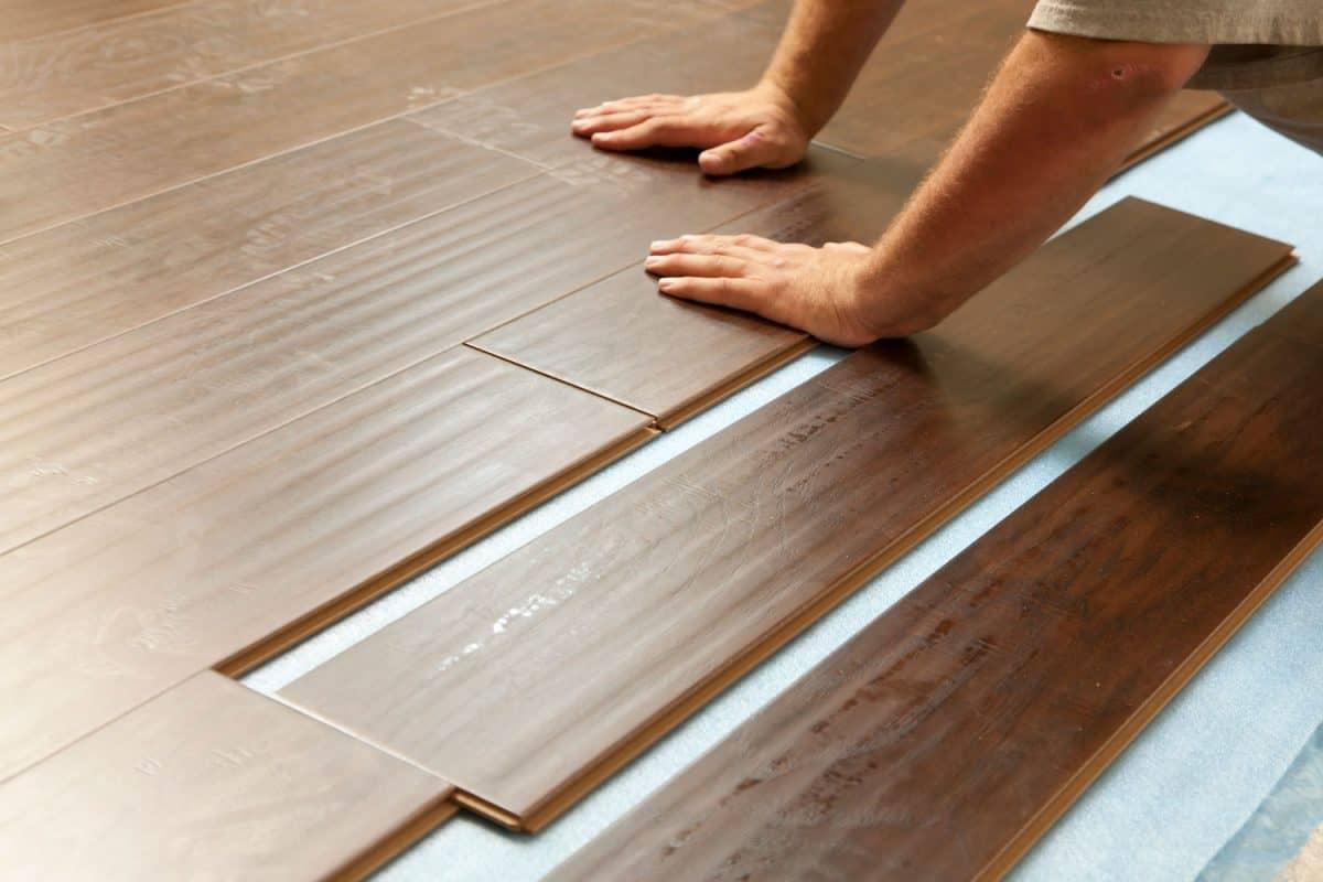 A tile installer inserting wooden laminated flooring on the floor