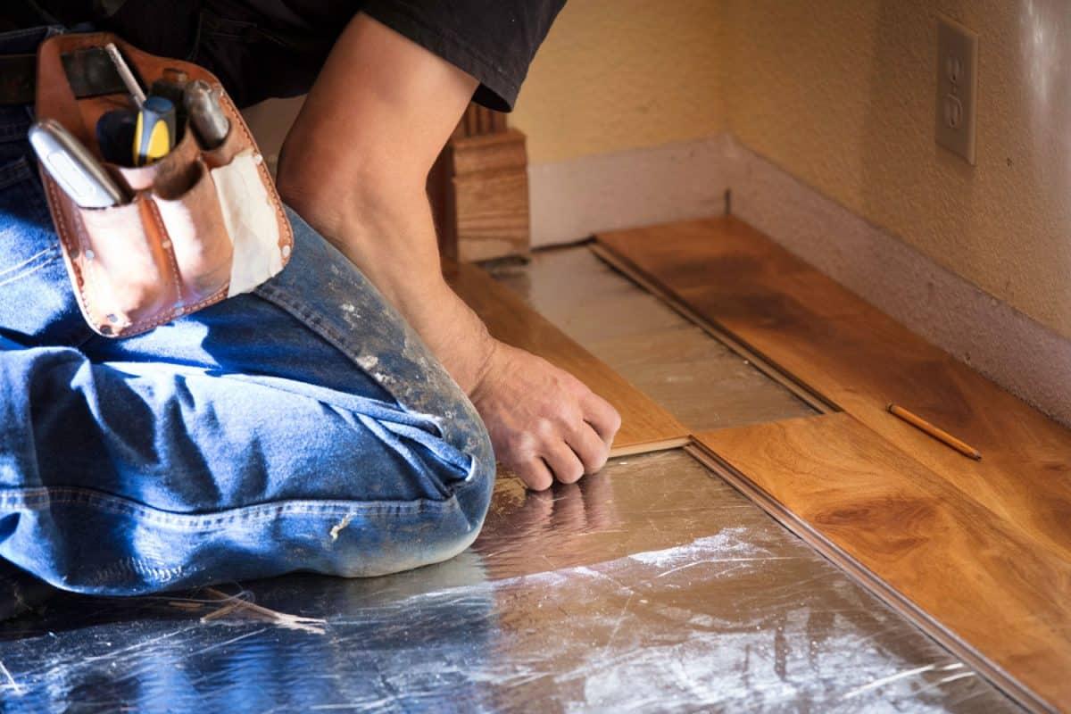 A tile setter inserting a hardwood tile on the flooring