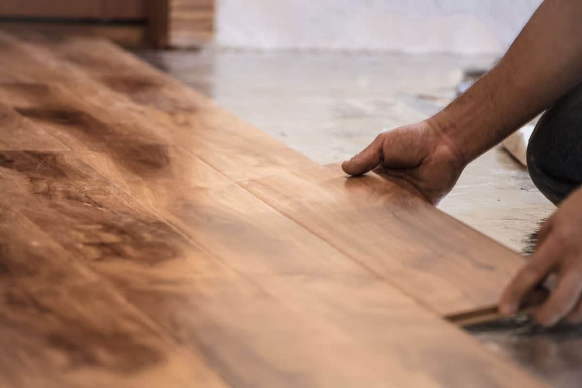 A tile setter installing hardwood flooring