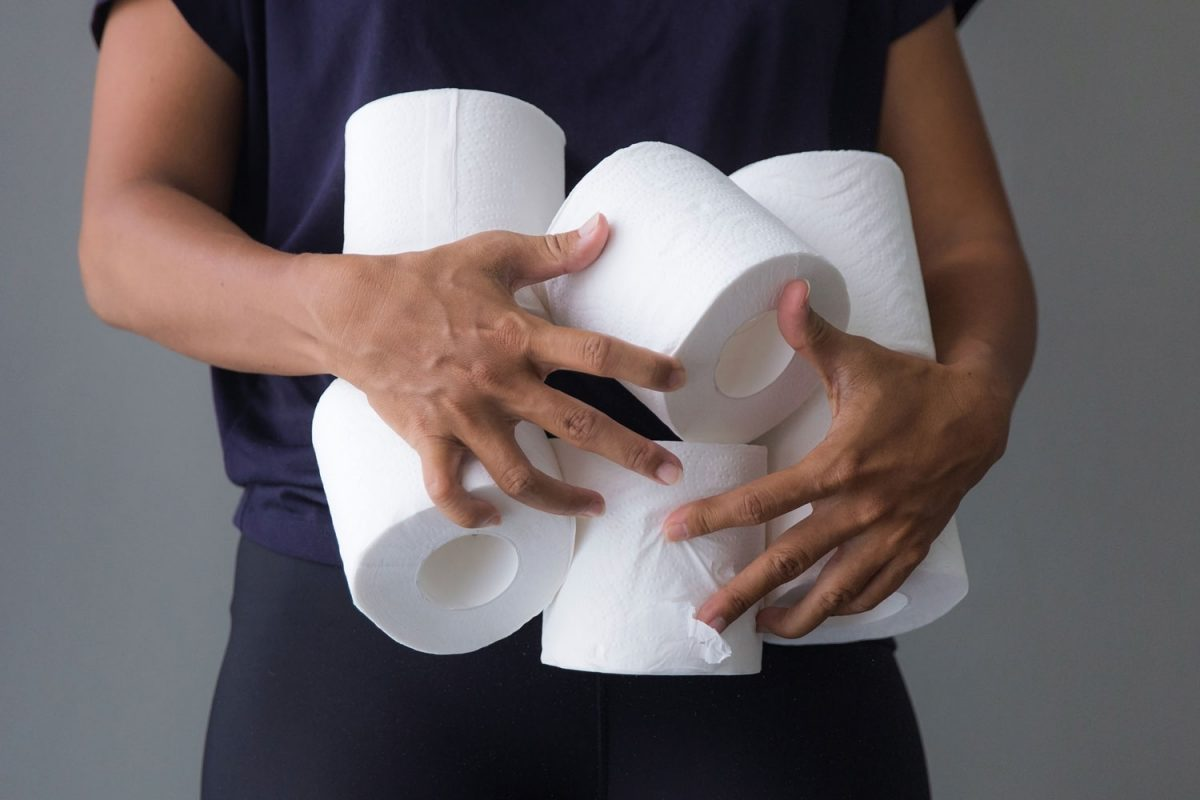 A woman holding six pieces of new toilet papers