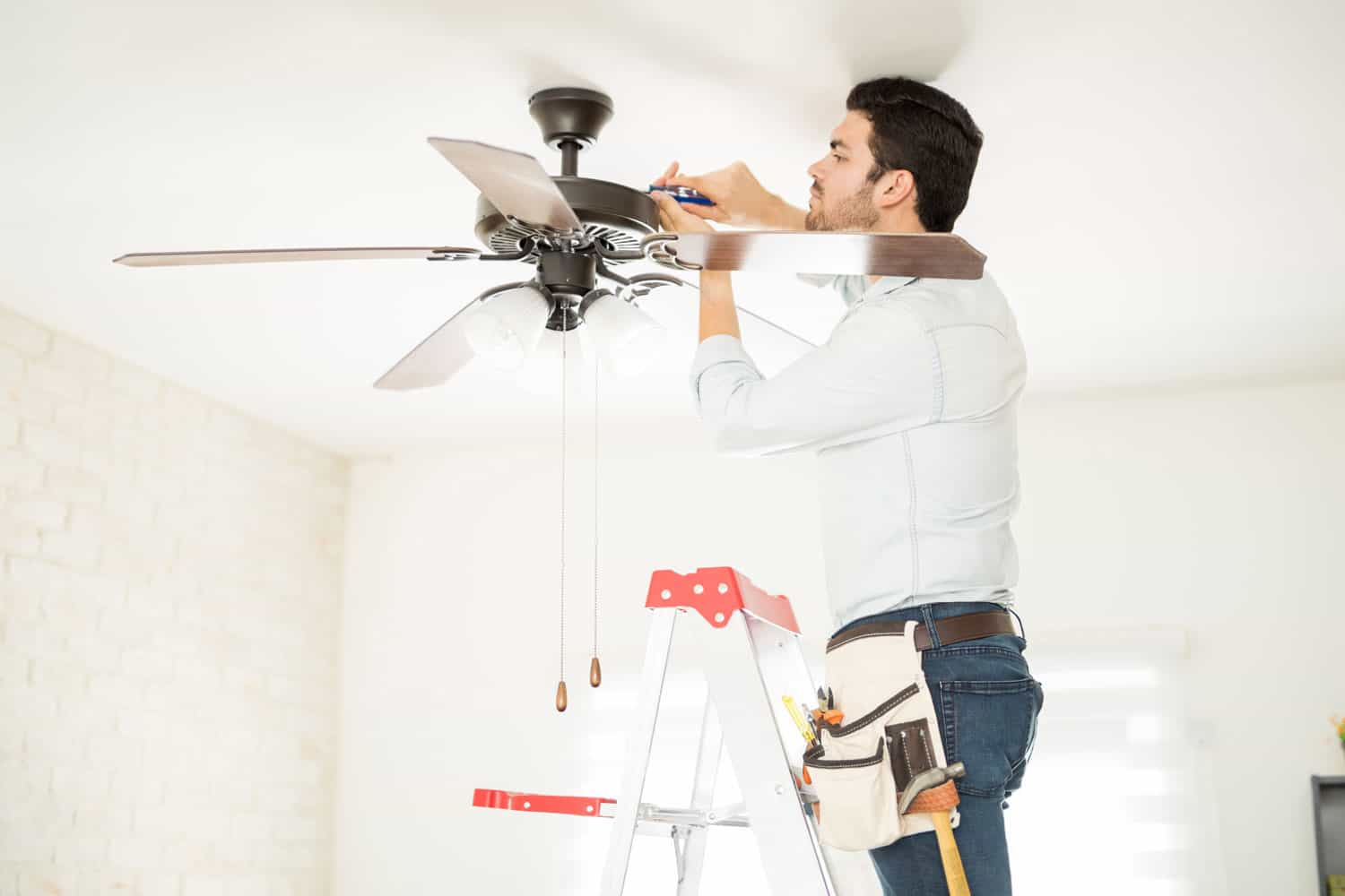 A worker doing repair work on the ceiling fan