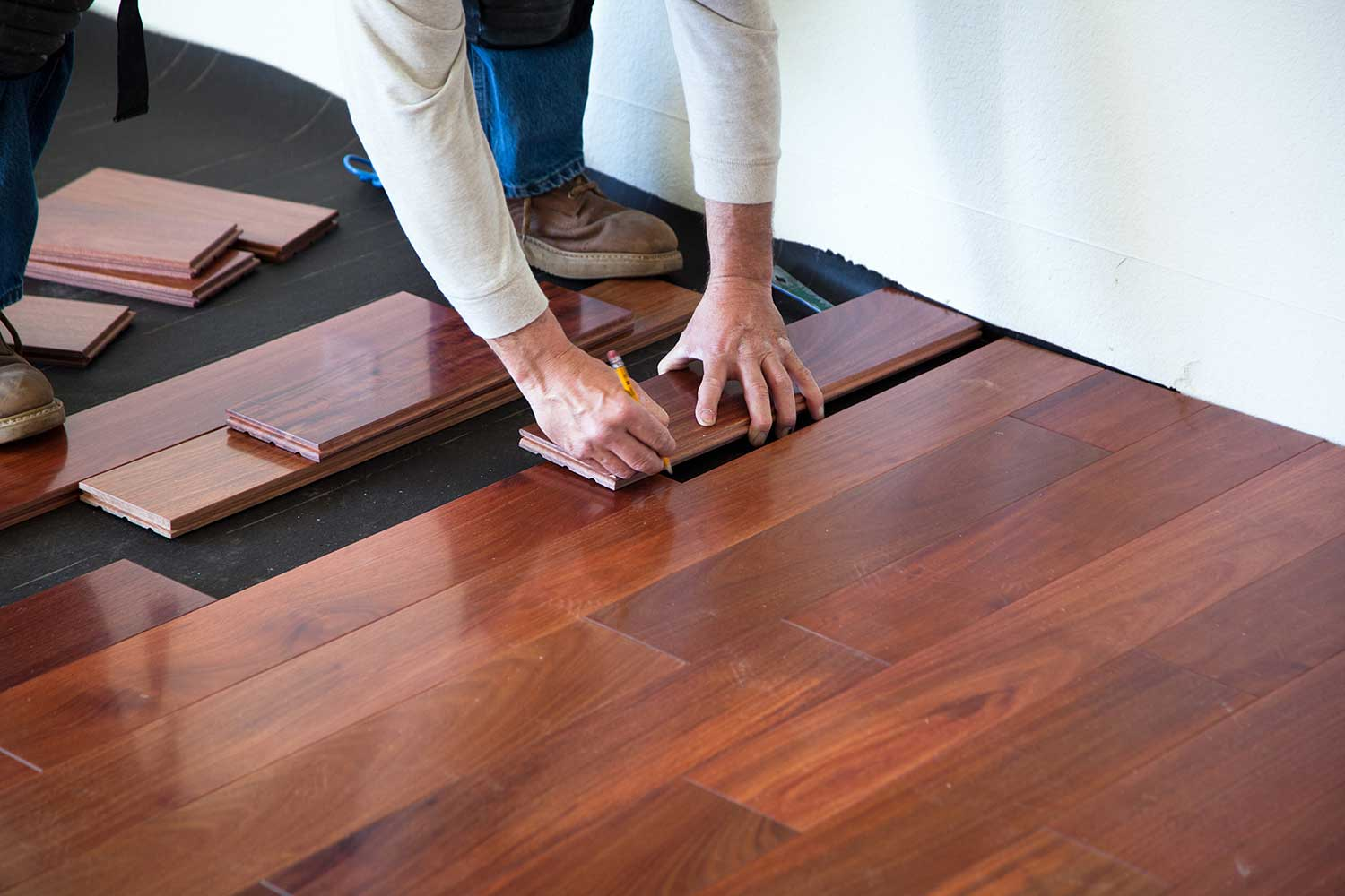 A worker installing hardwood floor in an American upscale home