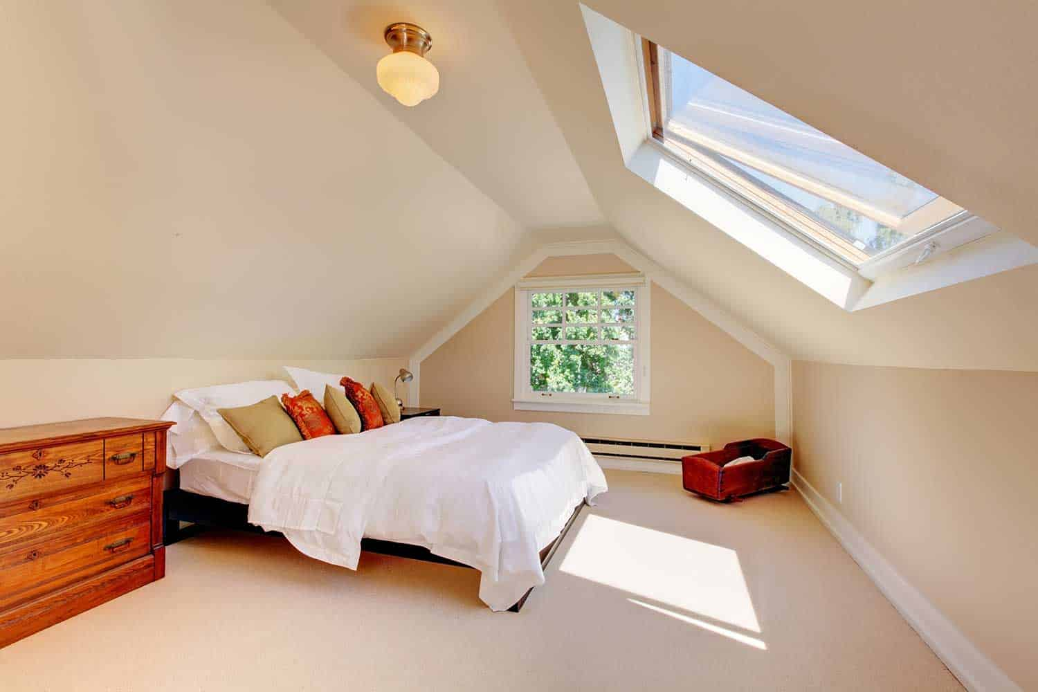 Attic modern bedroom with white bed and skylight