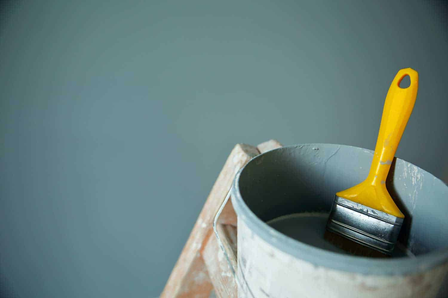 Bucket of paint and brush on wooden stairs