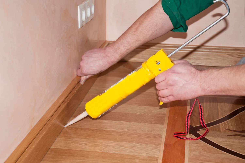 Carpenter on work putting wood parquet skirting board with caulking gun, Should You Caulk Between Baseboard And Floor?