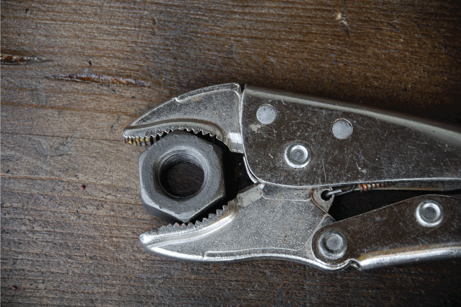 Close up locking pliers on wooden background