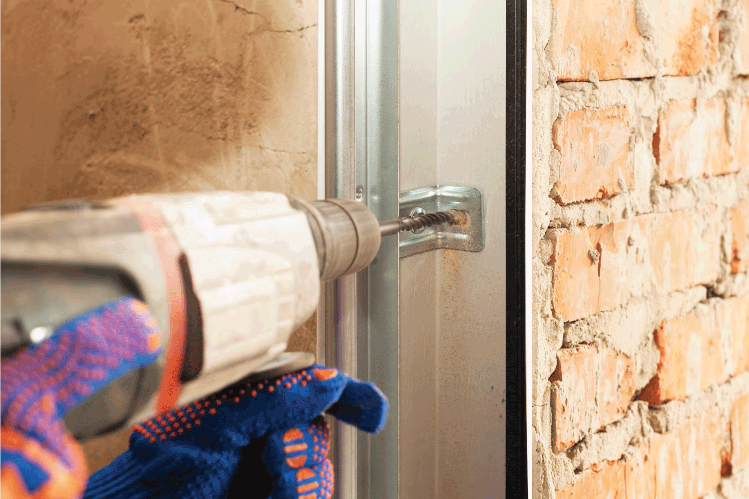 Concept of replacement details. Cropped view of professional worker using electric drill, making hole in brick wall and install new metal rail on garage door system in house under construction