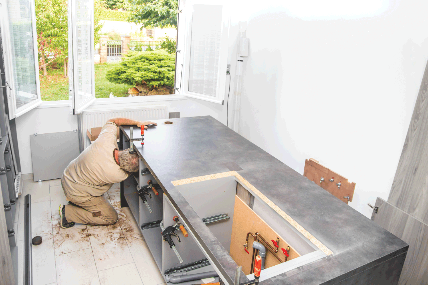 Fitter, manual construction worker man, installing integrated kitchen furniture with clamps and plumbing in a new kitchen custom made with opened window