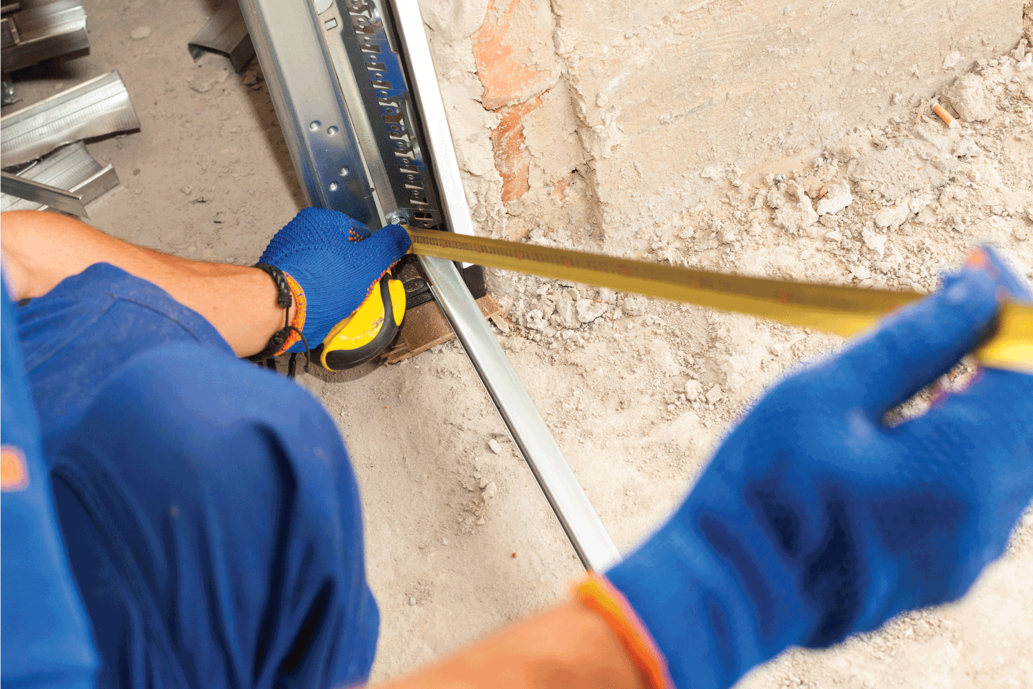 Garage Door Installation. Worker use a ruler to verify correct installation of metal profile