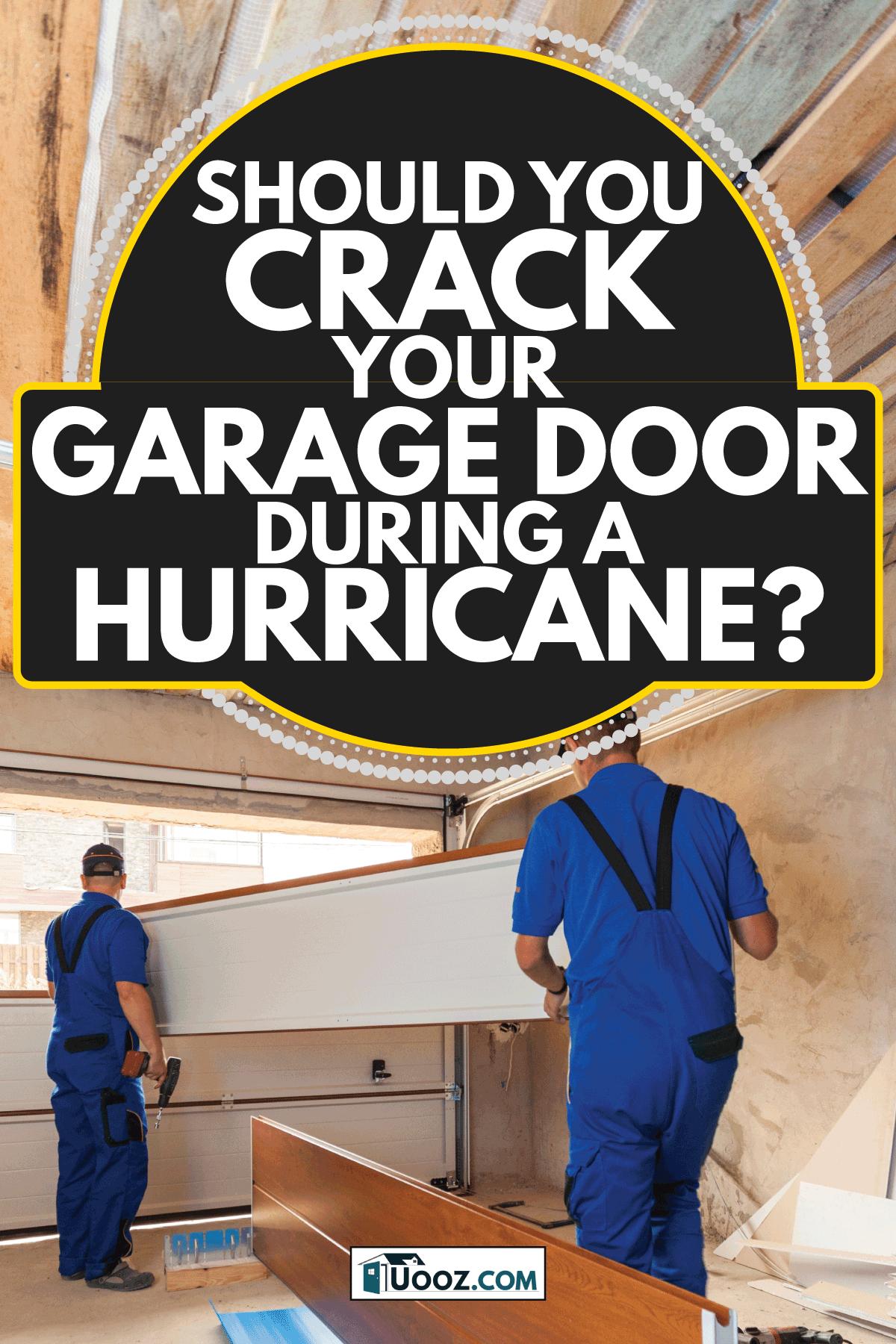 Garage doors installation.Workers installing lifting system. Should You Crack Your Garage Door During A Hurricane