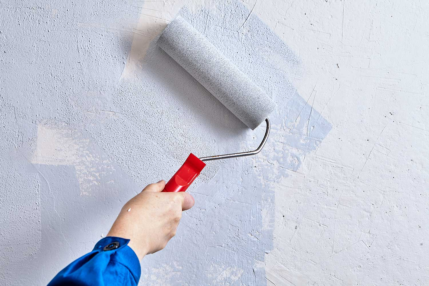 Home painter is painting walls with paint roller
