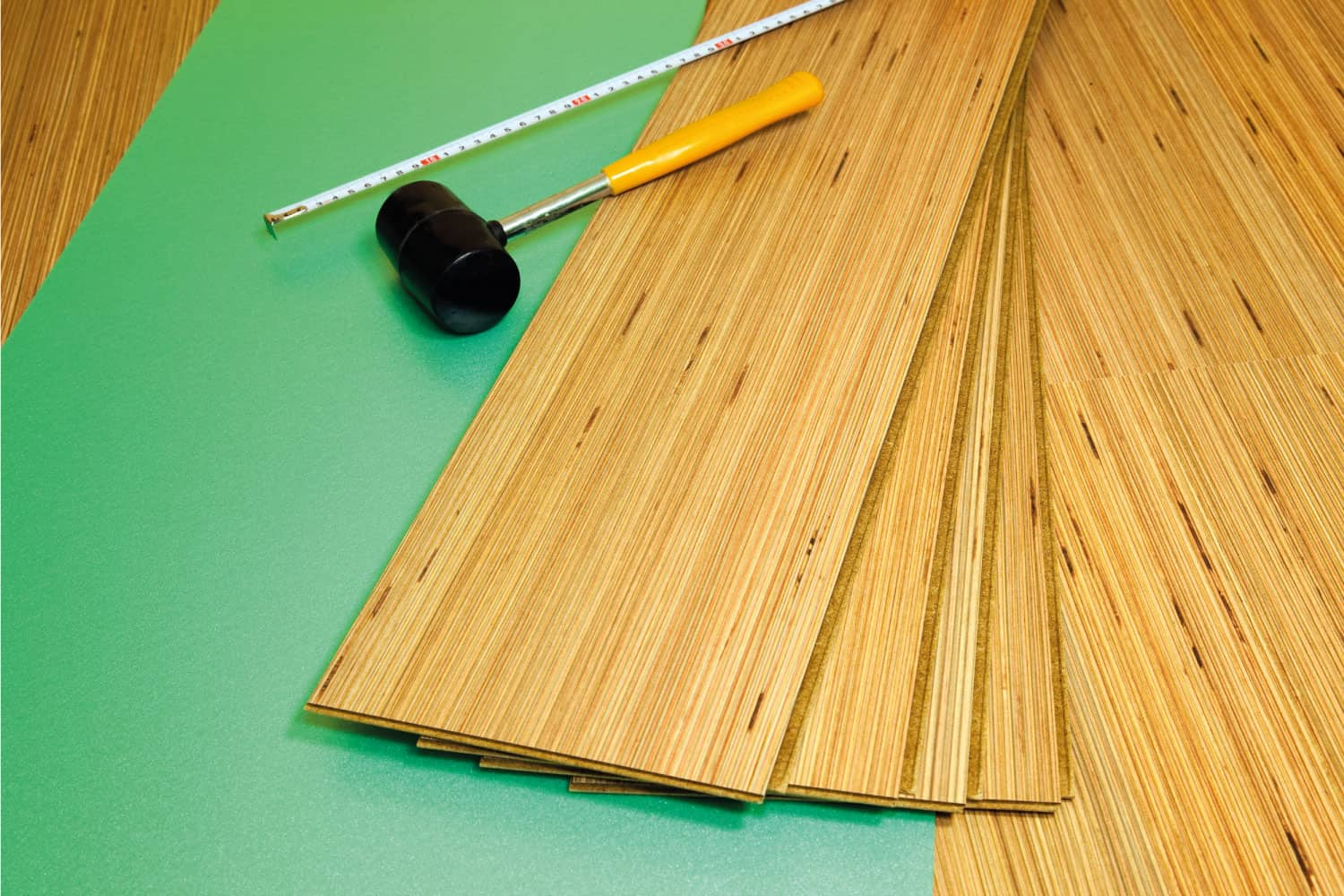 Laminate carpentry, light-brown laminate wood style flooring with rubber mallet