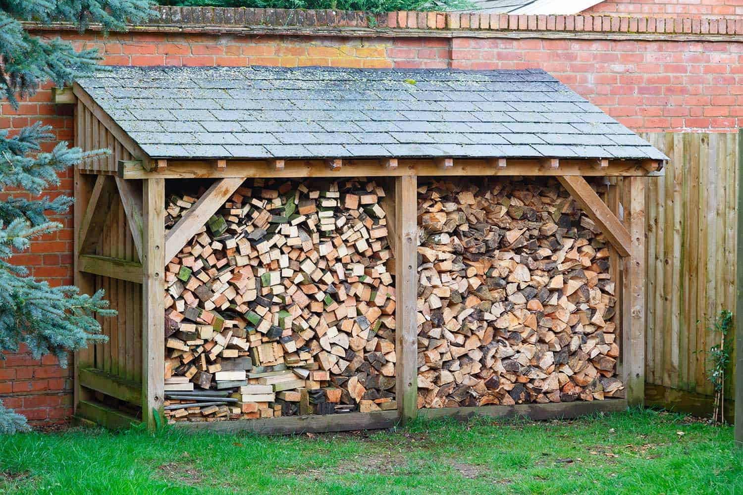 Large log store filled with firewood, timber construction with a slate roof