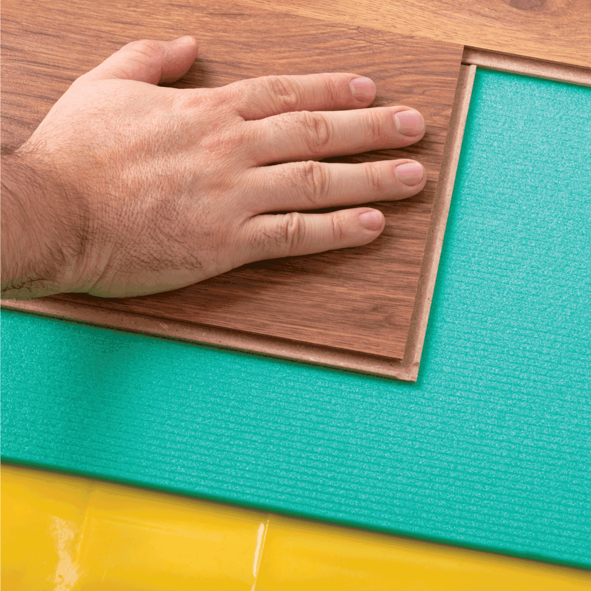 Laying Laminate Flooring. Yellow film vapor barrier and green foam underlayments. Person's hand seen putting the planks together