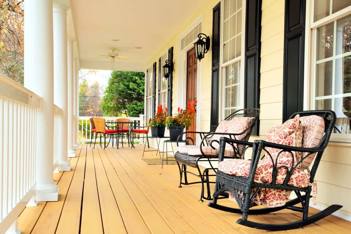 Low angle view of a large front porch with furniture and potted plants