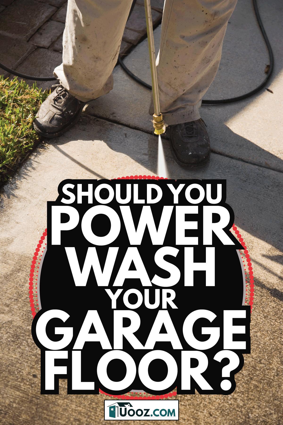 Man pressure cleaning sidewalk near garage. Should You Power Wash Your Garage Floor