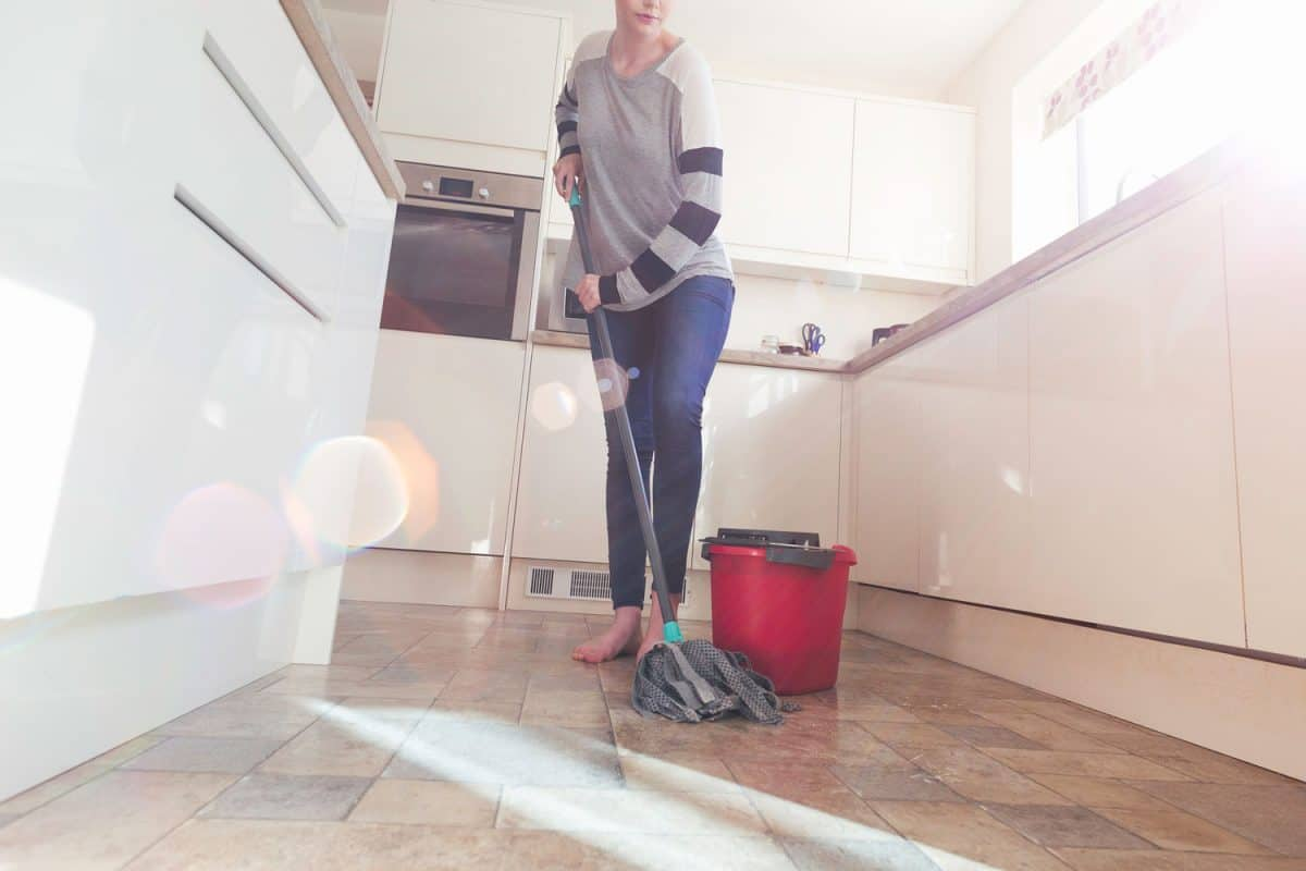 One woman mopping the floor in her kitchen, How Often Should You Mop Your Kitchen Floor?
