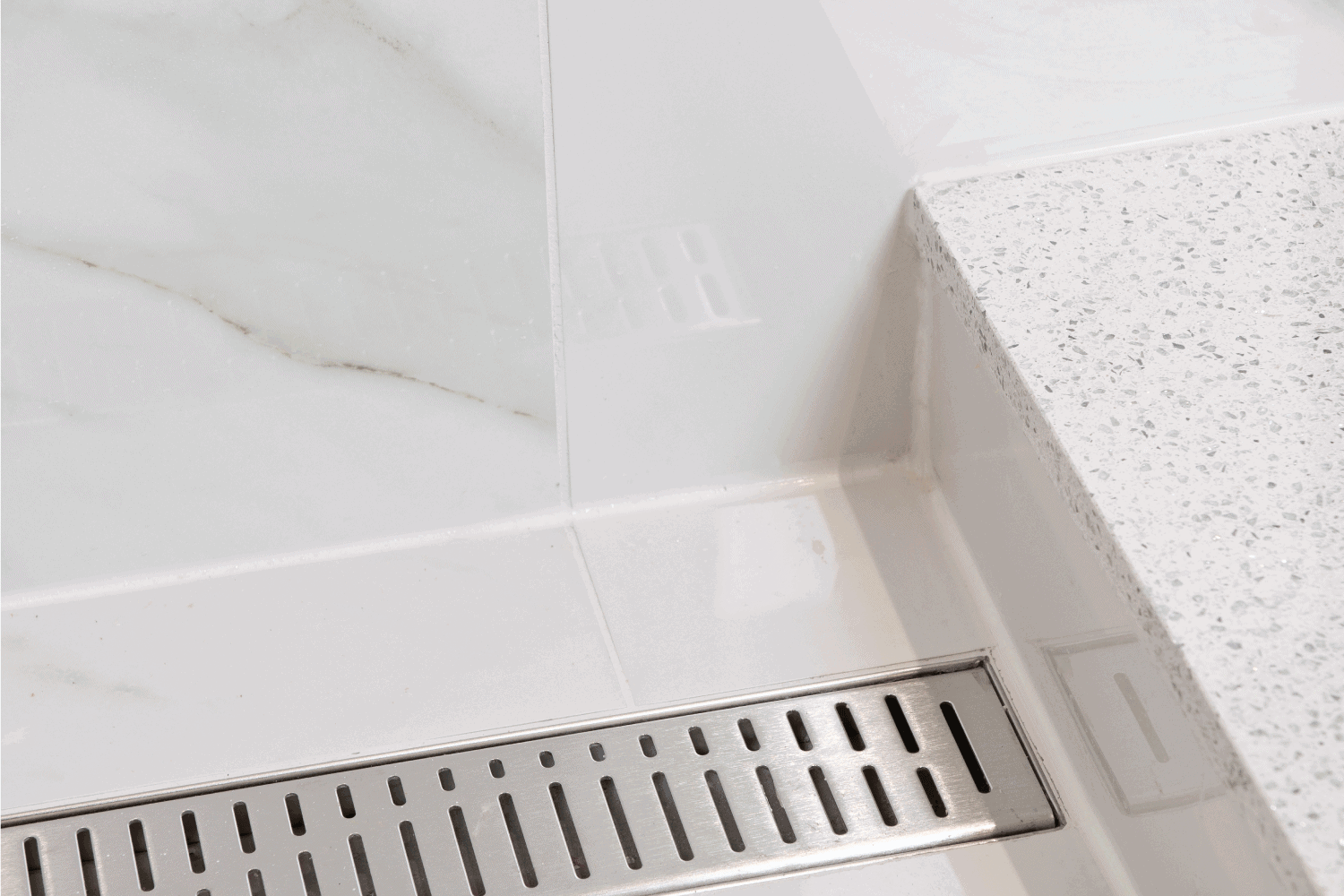 Rectangle Shower Drain in White Tile with a White Sill. Custom Luxury Shower.