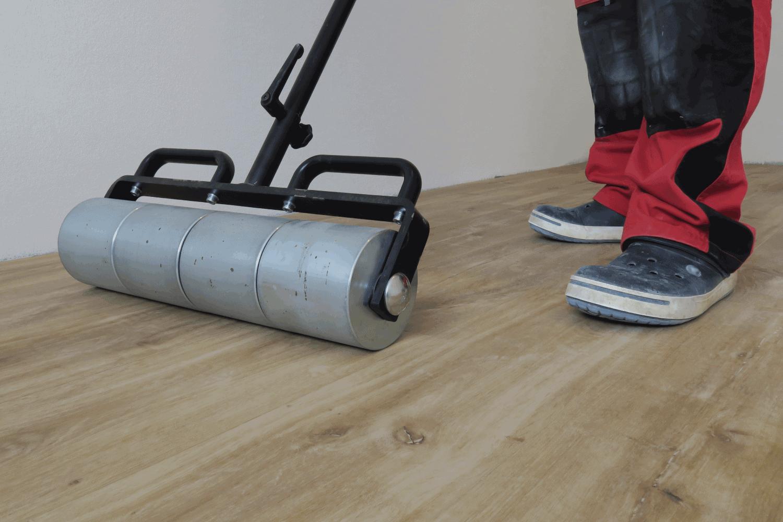 Rolling vinyl flooring using large steel roller