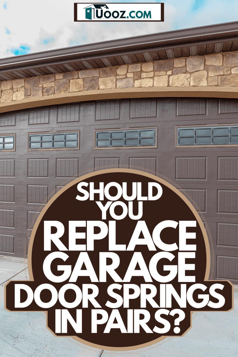 A huge brown colored garage door with decorative stones, Should You Replace Garage Door Springs In Pairs?