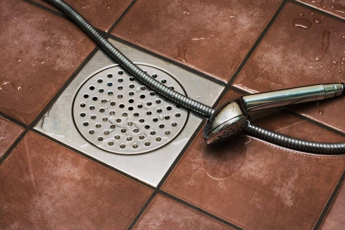 Shower drain and shower head in bathroom floor, 4 Types Of Floor Drains To Know