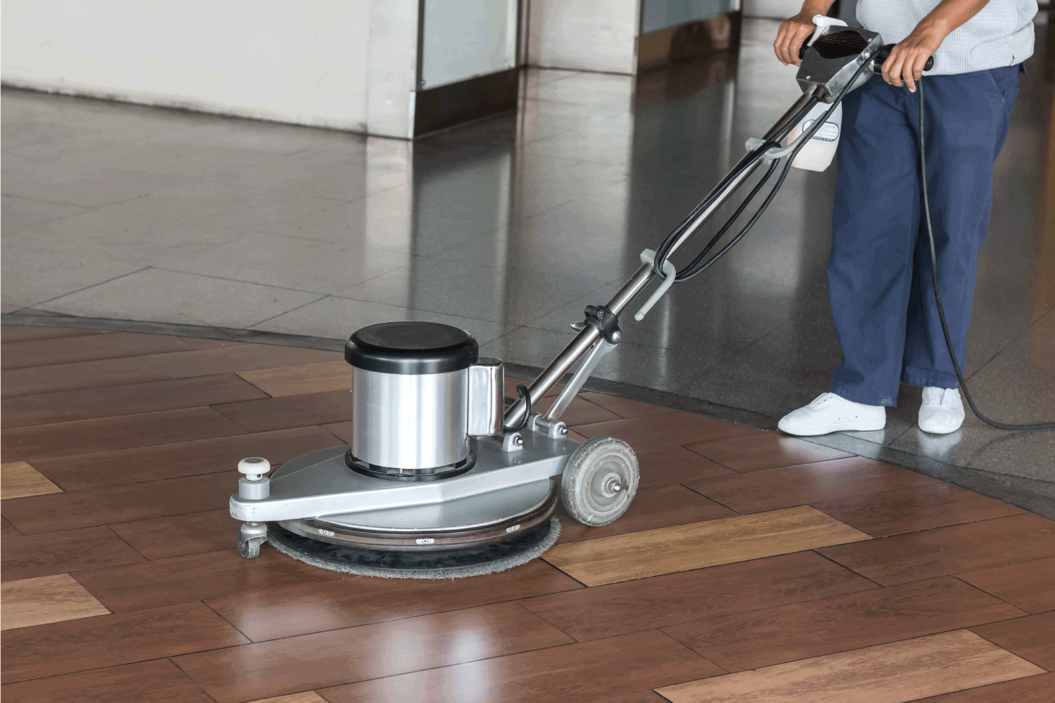 Woman cleaning the floor with polishing machine.