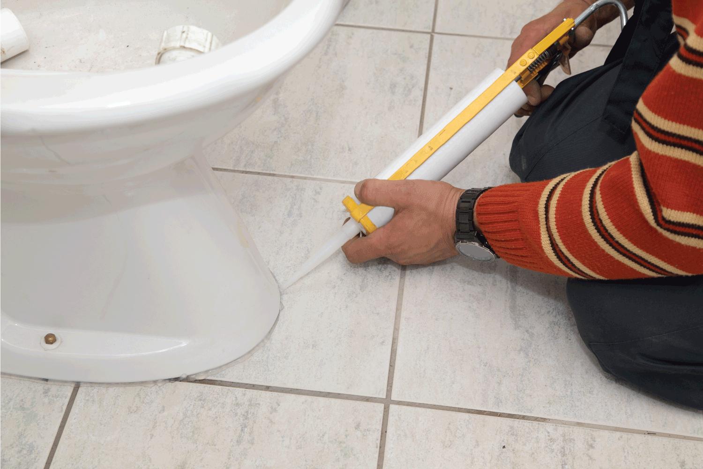 plumber caulking toilet seat to the tiled floor