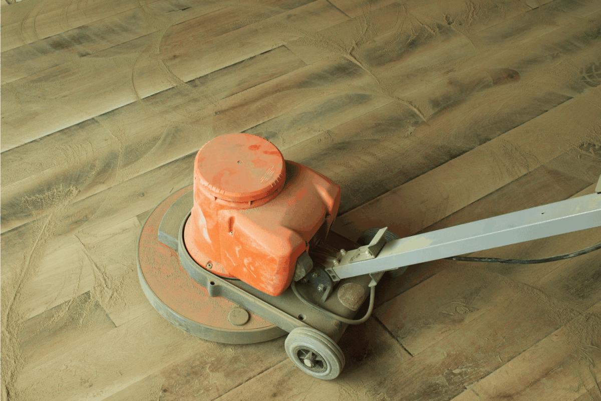 sanding wood floor using large equipment, dust everywhere