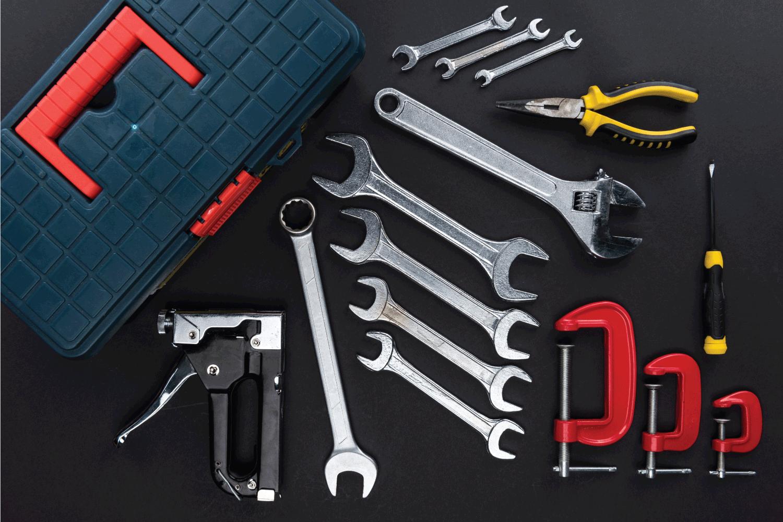 toolbox and repair tools laid on a dark mat