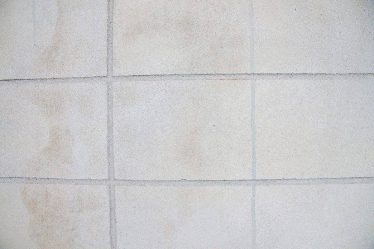 A detailed photo of tile flooring with cracking grout