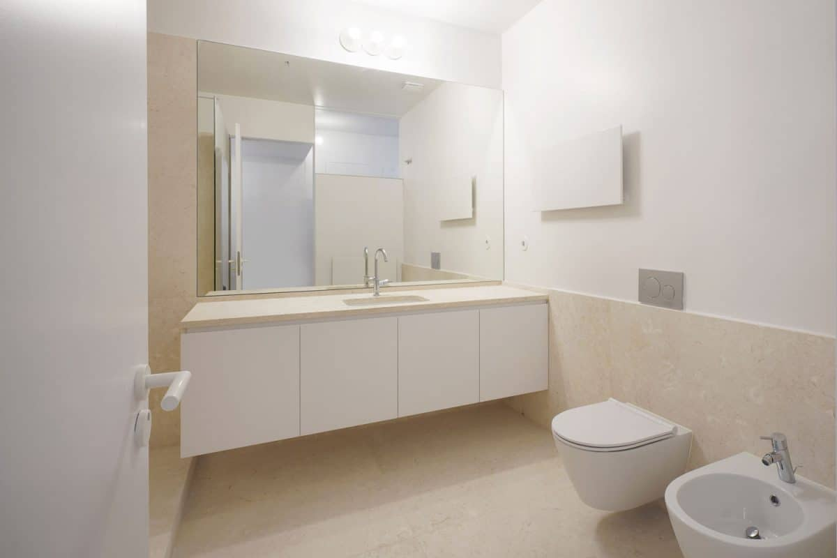A goregous white and modern bathroom with a white vanity area