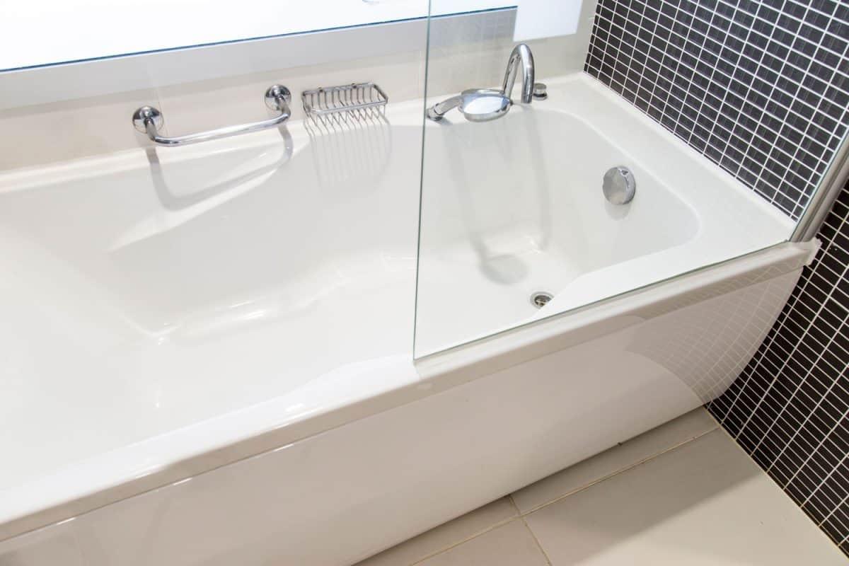 A huge ceramic bathtub inside a bathroom with small tiled backsplash, Can Bathtub Drain Pipes Freeze? [And How To Unfreeze Them]