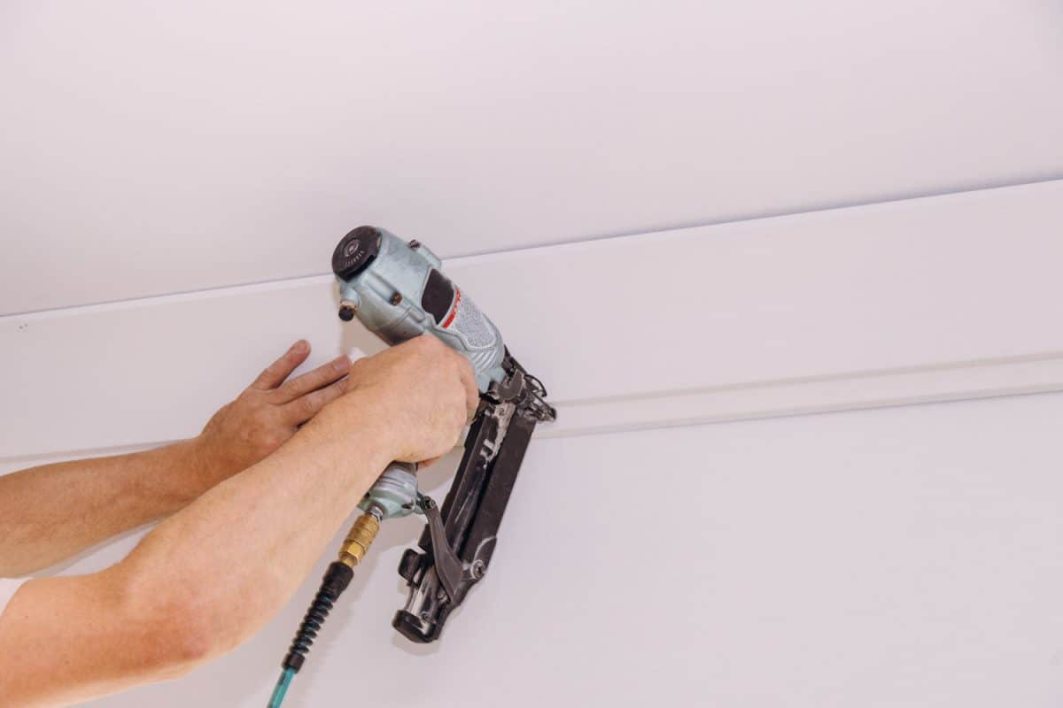 A man using a nail gun to install the trim, What Size Brad Nails Do I Need? [By Type Of Project]