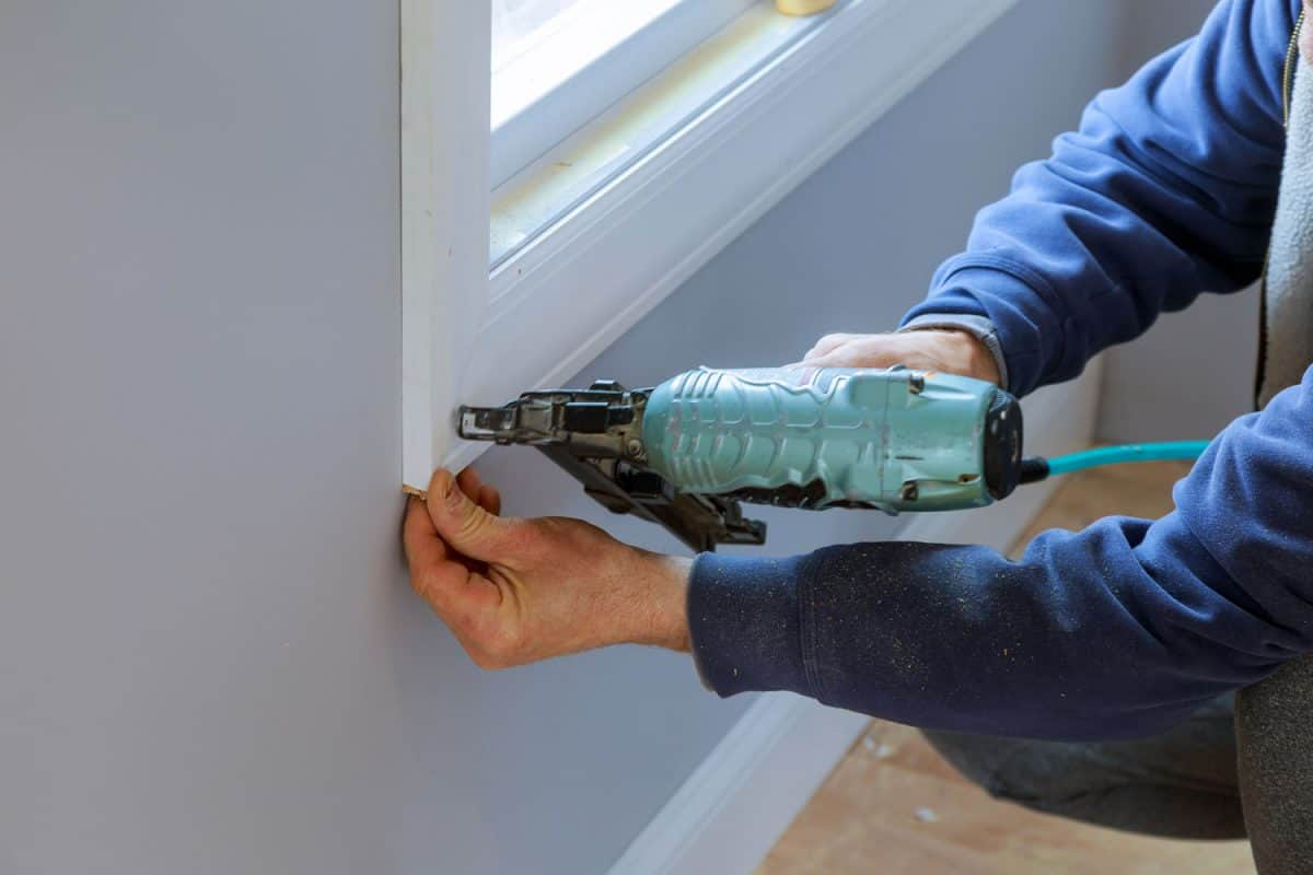 A man using a nail gun to nail into the wall in the window frame