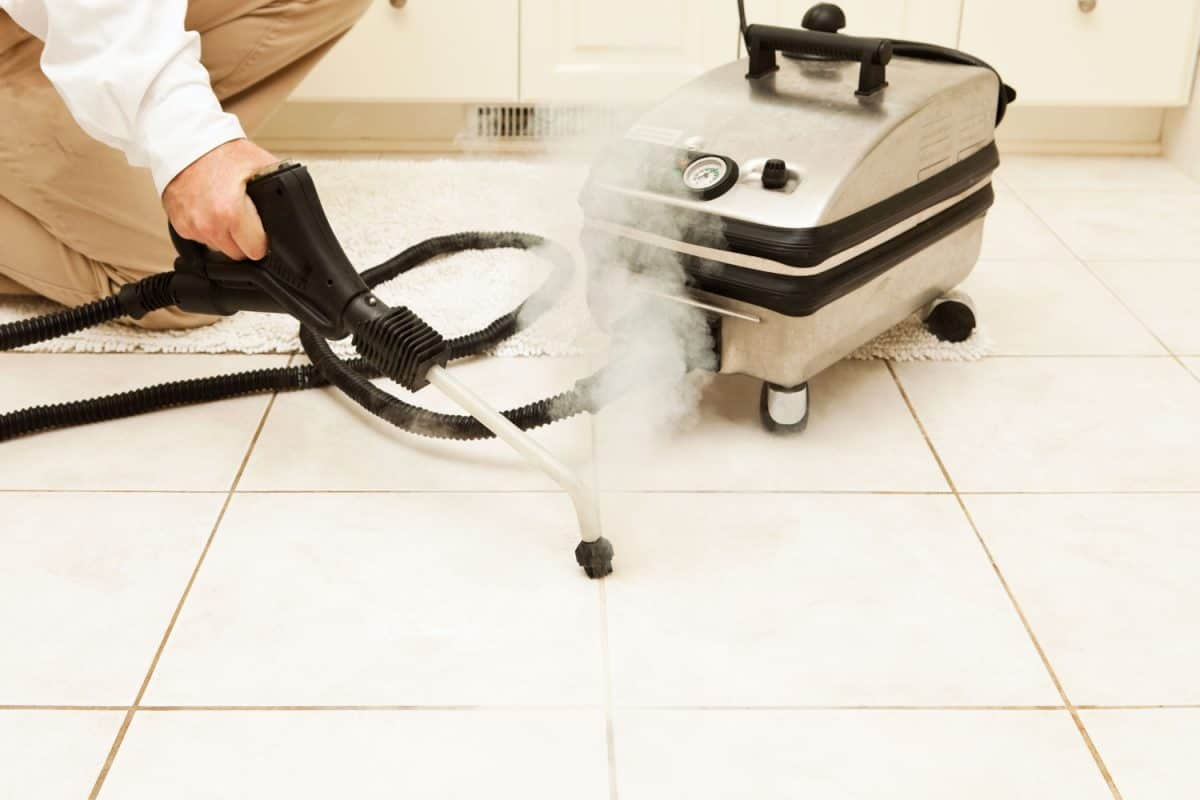 A man using a steam cleaner to clean the tile grout