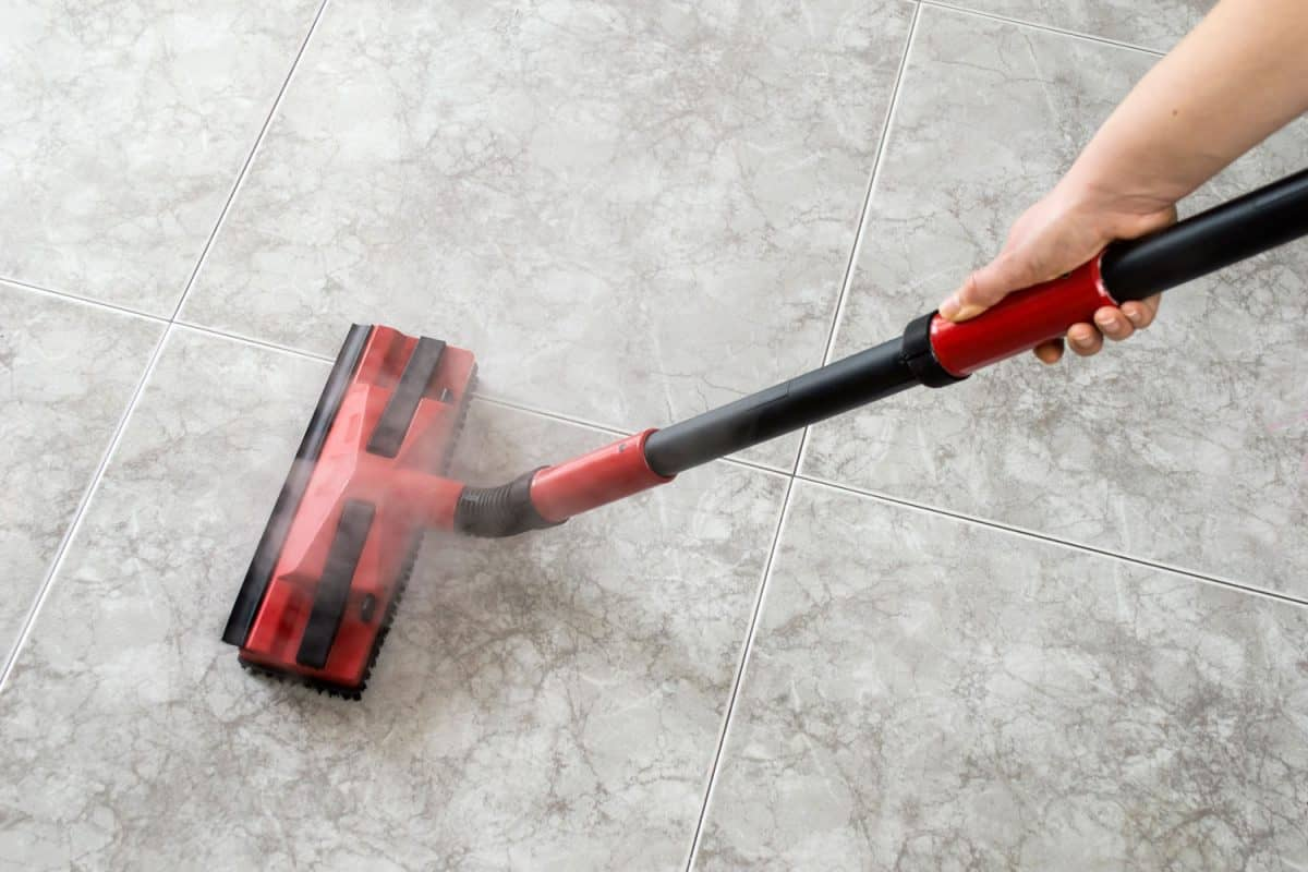 A man using a steam cleaner to remove the stain in the tile grout, Do Steam Cleaners Clean Floor Grout?