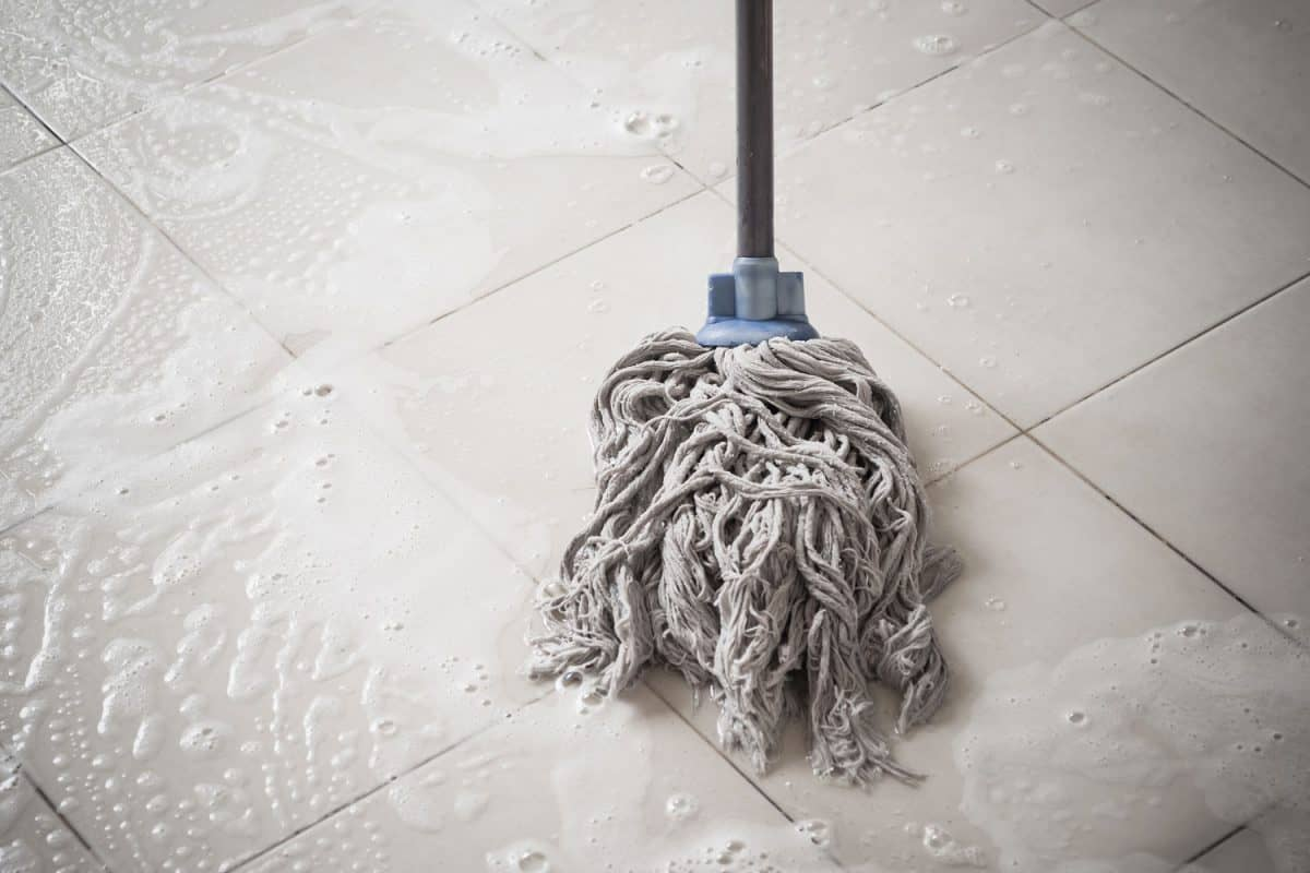 A mop washing a floor using bleach