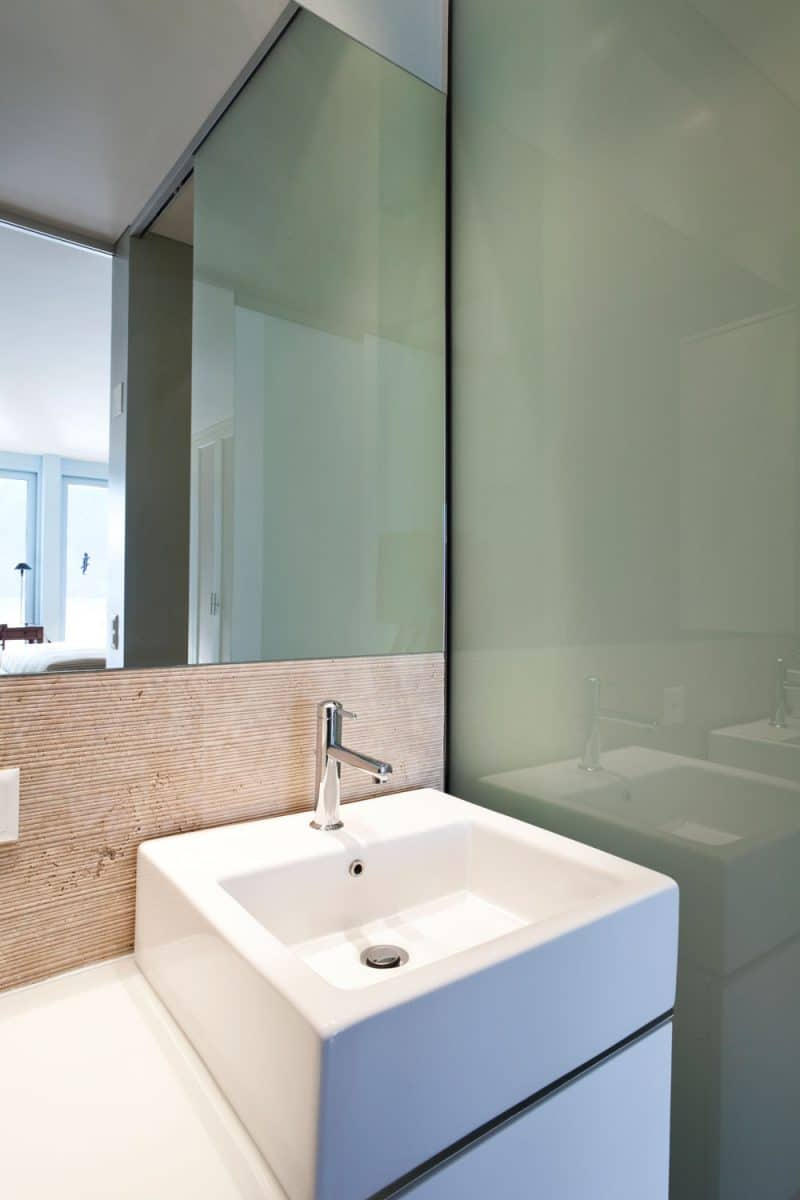 A small and narrow contemporary bathroom with a green gloss accent wall