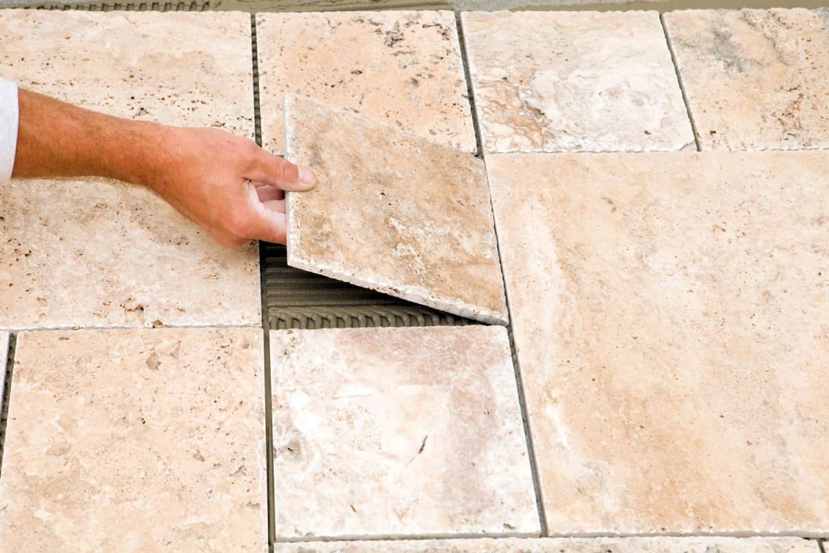 A tile worker placing the final place of tile on the floor