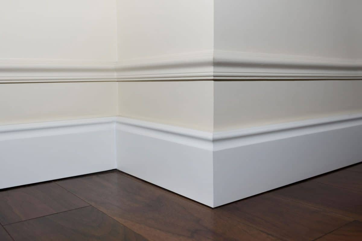 A white baseboard inside an off white painted wall and wooden flooring