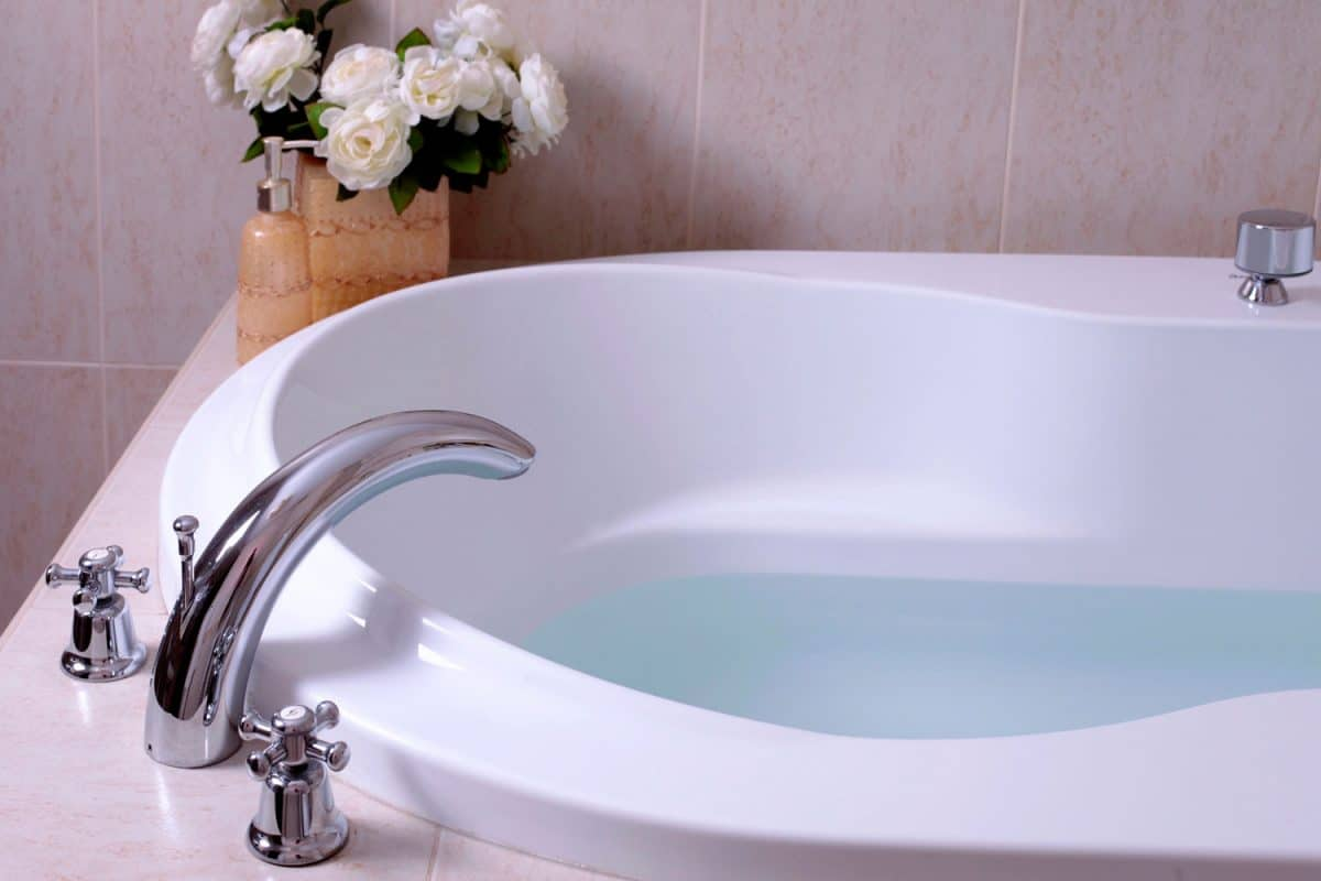 A white bathtub with beautiful chrysanthemum flowers on the side