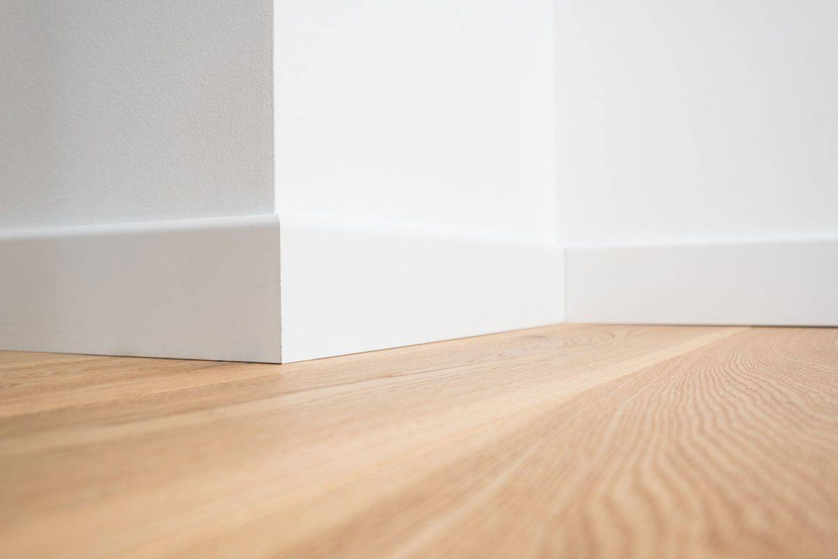A white painted living room with white painted baseboard and wooden flooring