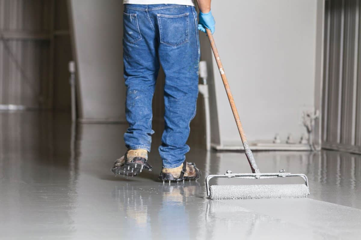 A worker applying epoxy on the flooring of a large warehouse or gym