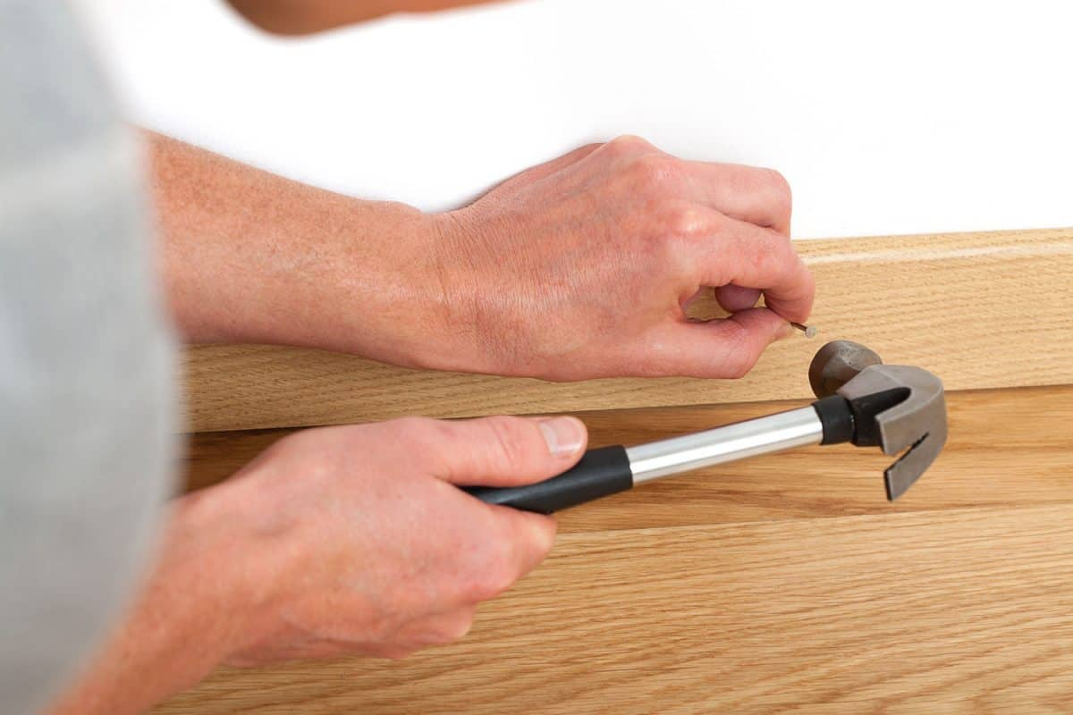 A worker making small alignments for the cabinets