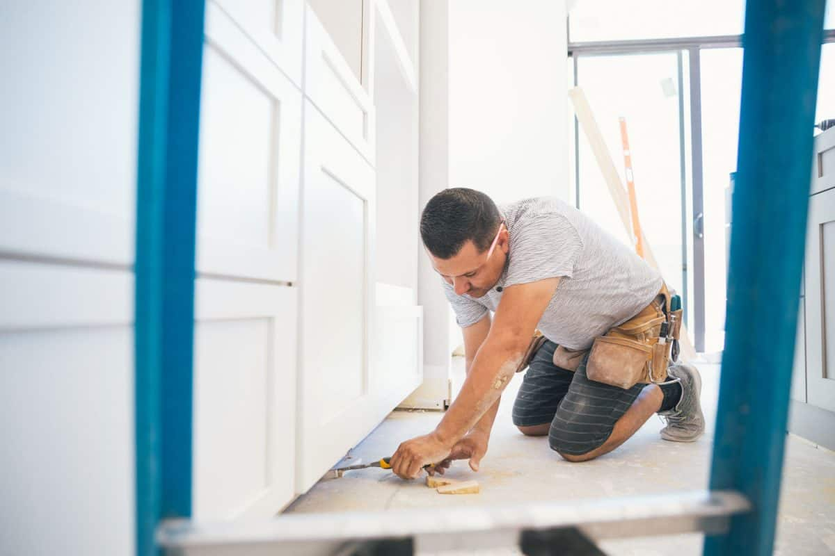 A worker measuring the flooring allotted for the cabinets