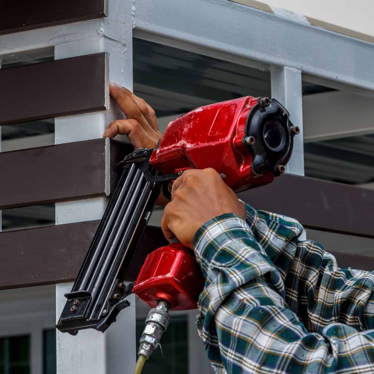 A worker using red colored nail gun to shoot nails to wooden framing