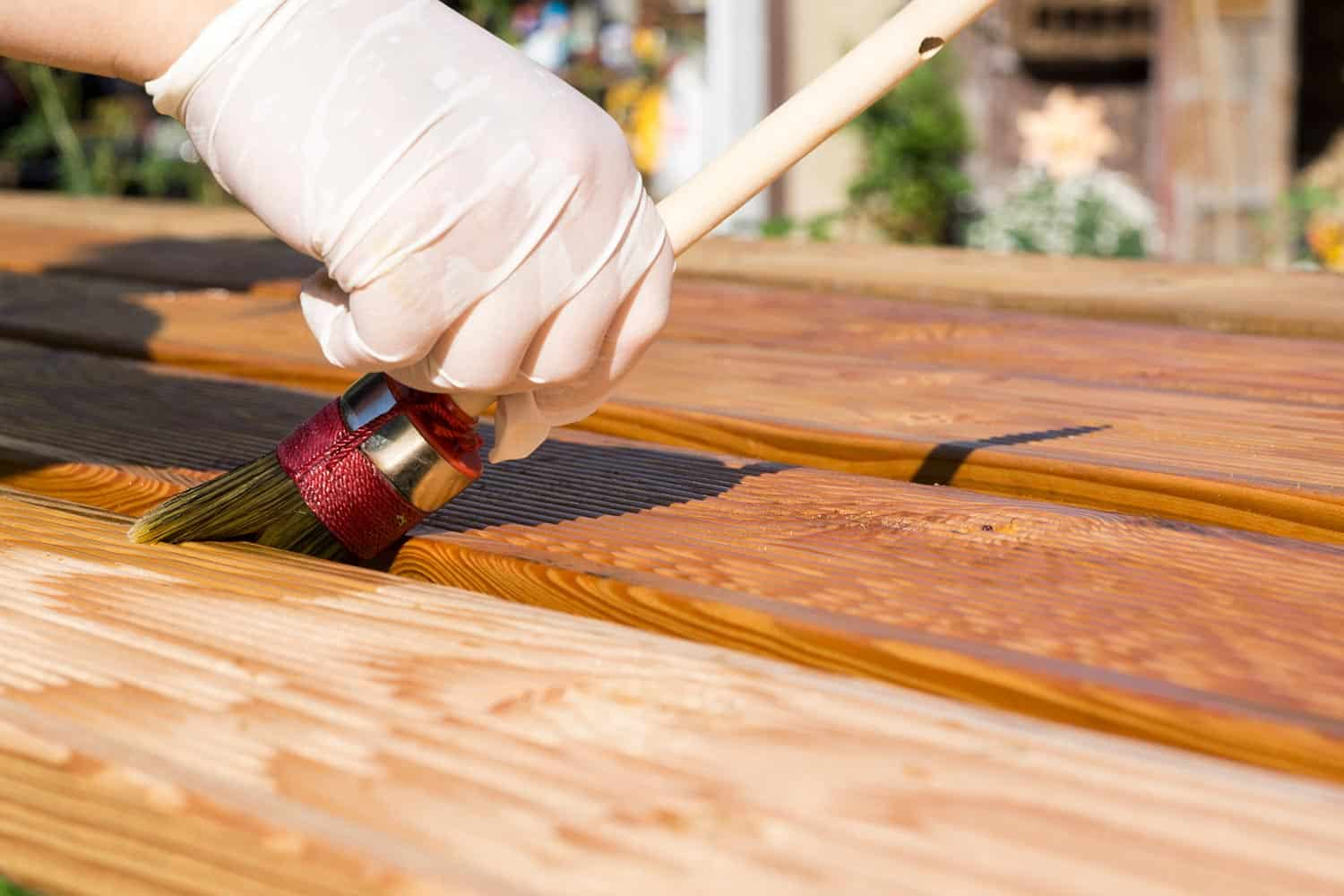 Applying protective varnish or wood oil on a wooden boards