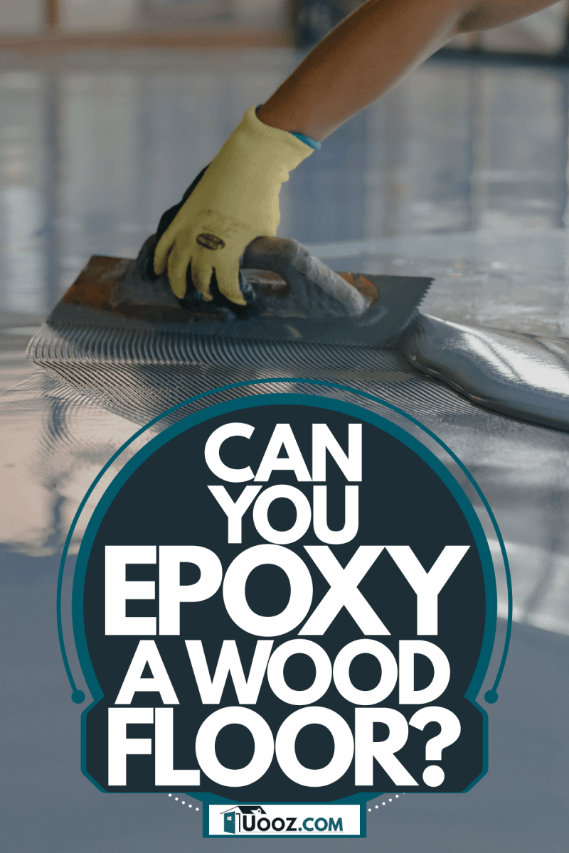 A worker applying epoxy on the stadium or gym floor, Can You Epoxy A Wood Floor?