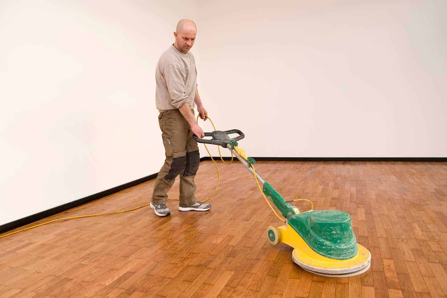 Carpenter polishing new parquet floor with wood oil using industrial polisher in an office
